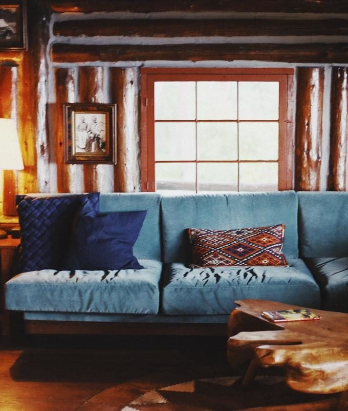 blue and brown leather padded 3-seated sofa in front of window panel